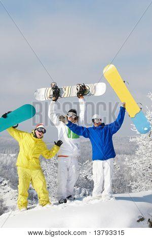 Portrait of joyful three snowboarders raising their boards