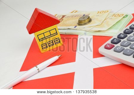 Danish Kroner notes and coins with a house calculator to represent property finance.