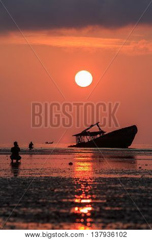 wreck boat sun rising sky and photographer at phuket thailand