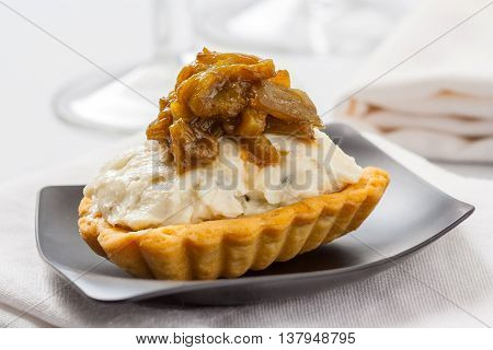 A tartlet appetizer with blue cheese and onion confit.