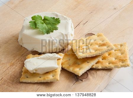 Fresh natural cream cheese with crackers on a wooden cutting board.