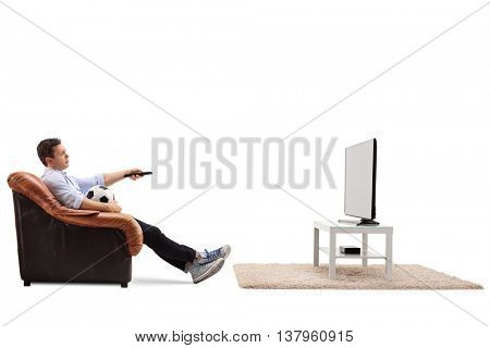 Bored young guy watching football on TV and changing the channel isolated on white background