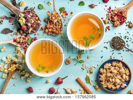 Two cups of healthy herbal tea with mint, cinnamon, dried rose and camomile flowers in spoons over blue background, top view