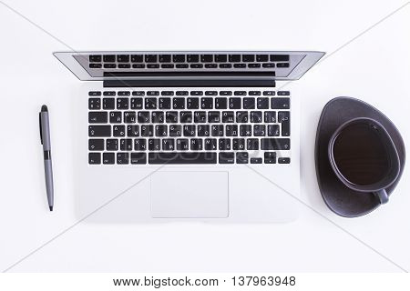 Top view of white office desktop with laptop pen and coffee cup