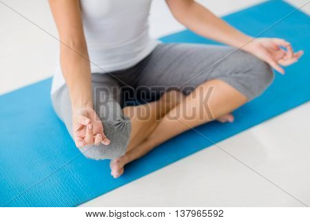 High angle view of woman doing yoga at fitness studio