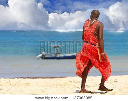 A Masai Warrior dressed in red stands on a beach in Kenya looking out to sea and the cloudy blue sky