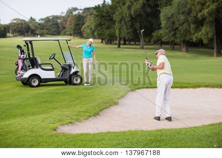 Mature golfer playing on sand trap by woman at golf course