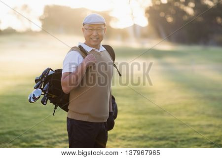 Portrait of man carrying golf bag while standing on grassy field