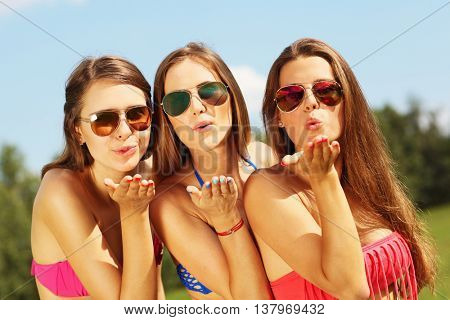 Picture presenting a group of women in bikin sending kisses