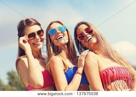 Picture presenting a group of women in bikin having fun outdoors