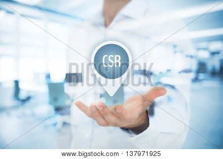 Corporate social responsibility (CSR) concept. Businessman hold virtual label with text CSR double exposed with office in background.