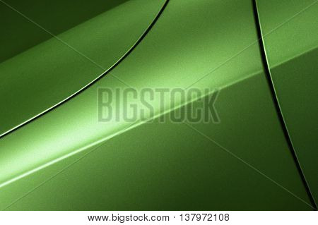 Surface of green sport sedan car, detail of metal hood, fender and door of vehicle bodywork