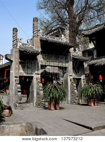 Jie Zi Ancient Town China - March 6 2013: handsome gray stone entry gate leads into the town's main square and Jinyu Street