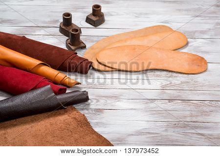 Set of leather in rolls craft tools on the white wooden background. Workplace for shoemaker. Working handmade tools on a work table.
