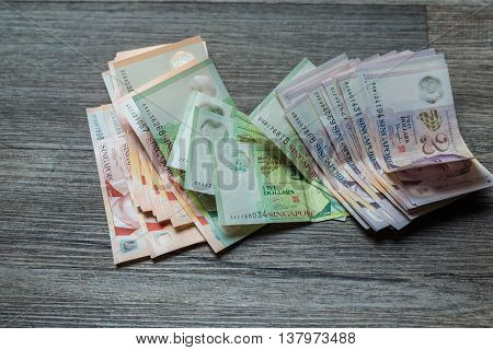 Singapore Currency Spread On Wood Background.