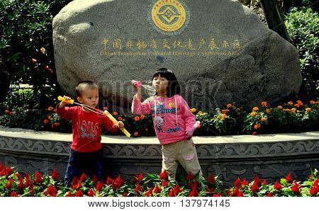 Jie Zi Ancient Town China - October 1 2010: Two small children blowing bubbles in front of a boulder with gilded letters proclaiming Jiezi to be a China Intangible Cultural Heritage Exhibition Area