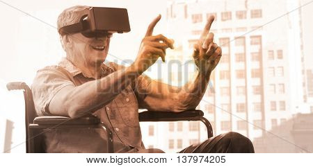 Senior man holding virtual glasses sitting on his wheelchair against low angle view of city buildings