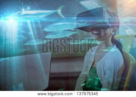 Fish swimming with shark in darkest water against seated girl wearing virtual reality glasses