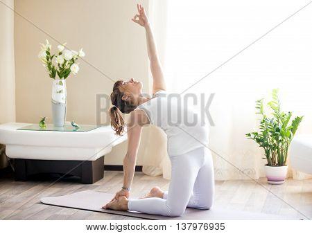 Pregnant Woman Doing Ustrasana Yoga Pose At Home