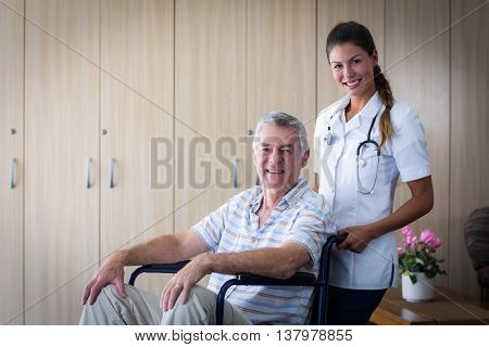 Portrait of smiling senior man and female doctor in living room at home
