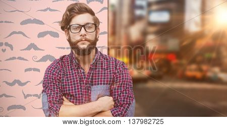 Confident hipster wearing eye glasses with arms crossed against composite image of mustaches