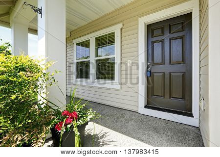 Open Porch With Concrete Floor, Column And Entrance Brown Door.