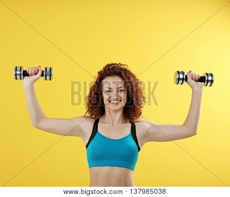 Attractive woman exercising with dumb bells on yellow background