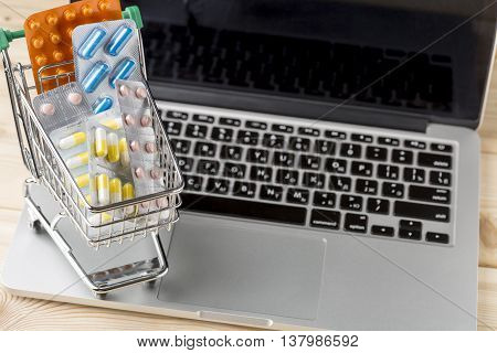 Mini shopping cart with pill blister pack on open laptop.Concept forn online store