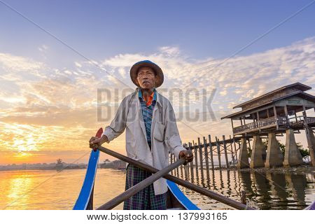 MANDALAY, MYANMAR - OCTOBER 28, 2015: A Gondolier paddles on Taungthaman Lake at U-Bein Bridge.