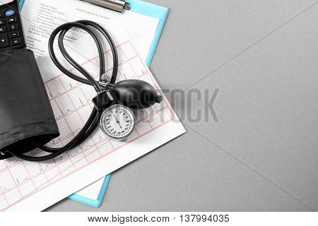 Tonometer with calculator and cardiogram on table