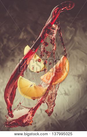 Sangria ingredients flying in wine splashes, closeup, toned