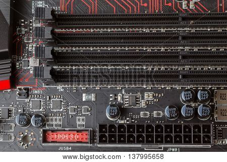 Mainboard DDR4 RAM socket. Black PCB with red lines.
