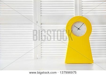 Stylish clock on white folding screen background