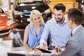 auto business, sale and people concept - happy couple with dealer buying car in auto show or salon poster