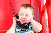 child speaks on the phone in noisy environments. kid hand closed his ears and squeezed his eyes shut while talking on the phone in a red telephone box. noisy surroundings, problem with phone connection poster