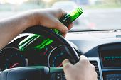 Drunk young man driving a car with a bottle of beer. Don't drink and drive concept. Driving under the influence. DUI, Driving while intoxicated. DWI poster