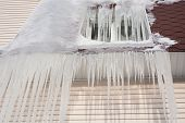 Frozen window. Icicles downspout on the brown roof. Cold weather conceptual image poster