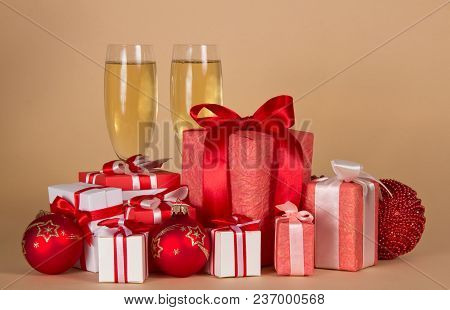 Lot Of Christmas Gifts In Different Beautiful Boxes, Glasses Of Champagne, On Beige Background