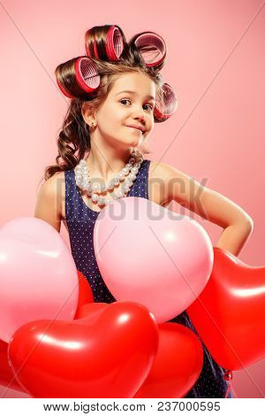Portrait of a pin-up little girl with curlers in her hair and balloons. Studio shot over pink background. Kid's fashion.