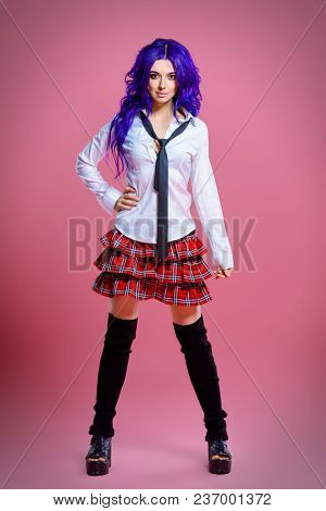Portrait of a student girl with purple hair in white blouse and checkered skirt posing at studio. Japanese style anime.