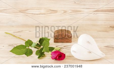 A Heart And A Rose With A Gift In Front Of A Wood Background