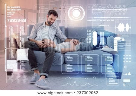 Peaceful Evening. Attentive Calm Cheerful Man Sitting On A Comfortable Sofa While His Tired Young Gi