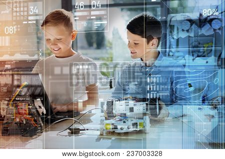 Clever Boys. Positive Friendly Classmates Smiling And Looking Interested While Looking At The Screen