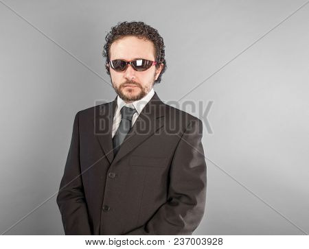 Serious confident businessman with red glasses in room. Looking in camera.