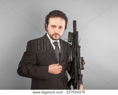 Serious confident businessman with machine gun in room. Looking in camera.