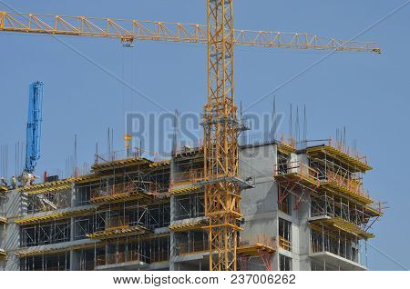 A Modern Building With Workers And A Crane Under Construction