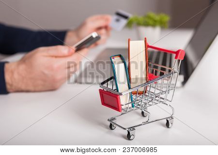 Online Purchase Of Books. Bank Card Nearby A Laptop And Mini Shopping Cart On White Background Top V