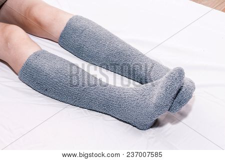 Woman Legs In Knee Socks On White Bed At Home