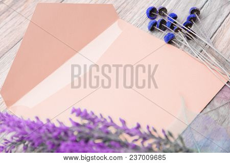 Light Envelope With Place For Text And Flowers On A Light Wooden Background