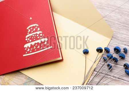 Red Greeting Card, Envelope And Flowers On A Light Wooden Background Closeup